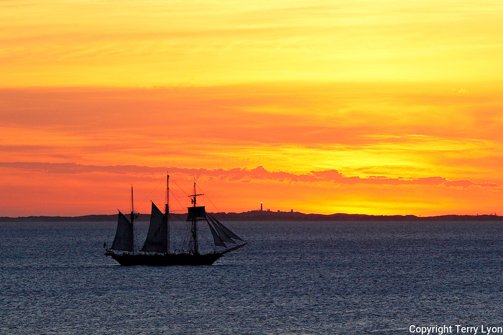 Sail training ship Leeuwin 2 sails past Rottnest island at sunset, view from Cottesloe beach