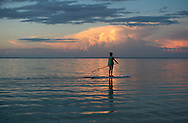 A woman on a paddle board at sunset on Le Morne Brabant Peninsula;  Mauritius, The Indian Ocean