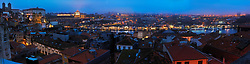 Panoramo of Porto at night, with a view over the Douro, the Dom Luis I bridge and the port houses.