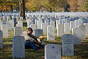 ARLINGTON, VA - NOVEMBER 11: Capt. Jeff Cliffe, with the U.S. Marine Corps, sits next to the grave of his grandfather and grandmother on Veteran's Day at Arlington National Cemetery on November 11, 2012 in Arlington, Virginia.