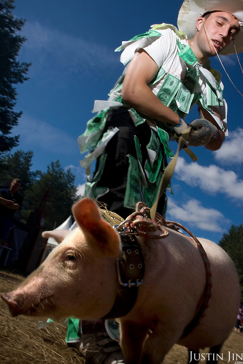 Pro-Putin Nashi youth Dmitry Ivanov, 20, dresses as Uncle Sam plastered with dollar bills and parading a pig at a summer camp on Lake Seliger in Russia. The yearly camp, organised by the nationalistic group, trains youth in political activism.