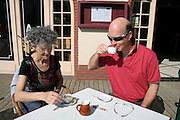 retired couple enjoying a coffee in the sun