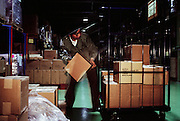 Kazuo Ukita moves books around the warehouse at his job at a distribution company. Like many other salary men, when Kazuo Ukita leaves home to catch the train for his job, he dons a navy blue suit for the hour-long commute, but changes into company work clothes once he arrives. During the commute, nearly all the men are dressed the same. Japan. Published in Material World: A Global Family Portrait, page 51. The Ukita family lives in a 1421 square foot wooden frame house in a suburb northwest of Tokyo called Kodaira City.