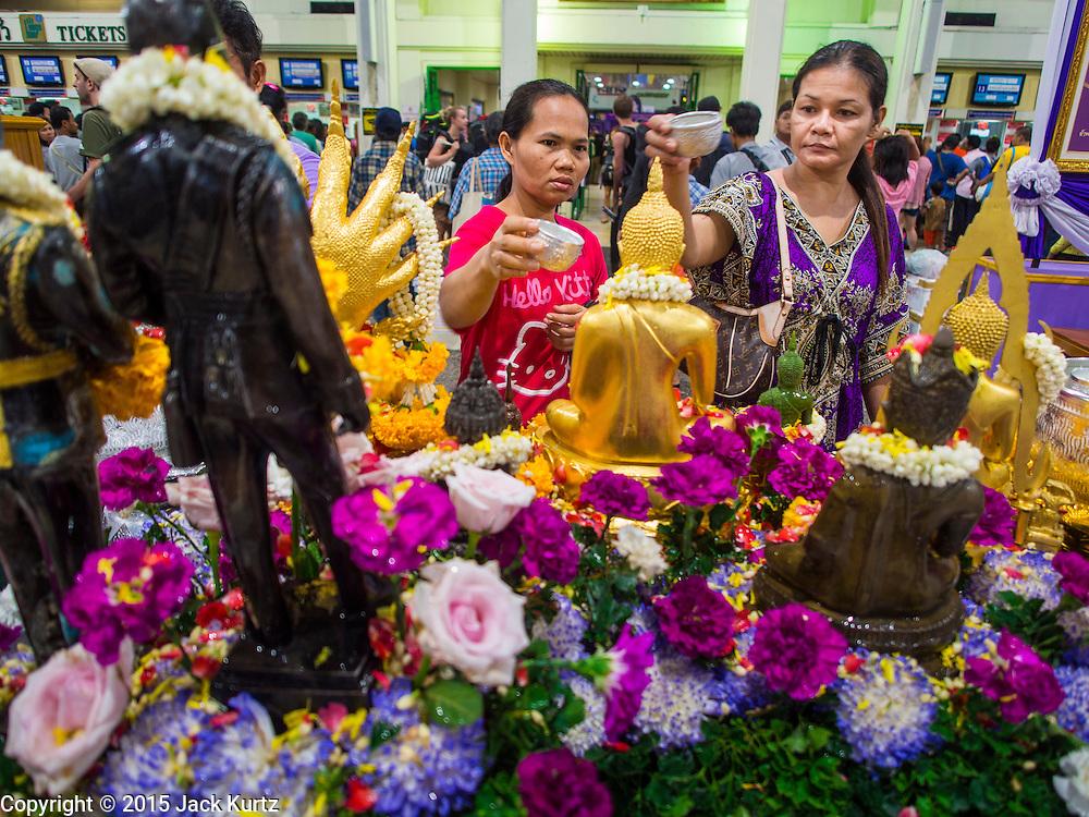 11 APRIL 2015 - BANGKOK, THAILAND:  People pray and make merit at a Buddhist alter set up for Songkran in Hua Lamphong train station in Bangkok. More than 130,000 passengers streamed through Bangkok's main train station Friday ahead of Songkran, Thailand's traditional new year celebration. Songkran will be celebrated April 13-15 but people started streaming out of Bangkok on April 10 to go back to their home provinces.   PHOTO BY JACK KURTZ