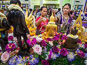 11 APRIL 2015 - BANGKOK, THAILAND:  People pray and make merit at a Buddhist alter set up for Songkran in Hua Lamphong train station in Bangkok. More than 130,000 passengers streamed through Bangkok's main train station Friday ahead of Songkran, Thailand's traditional new year celebration. Songkran will be celebrated April 13-15 but people started streaming out of Bangkok on April 10 to go back to their home provinces.   PHOTO BY JACK KURTZ