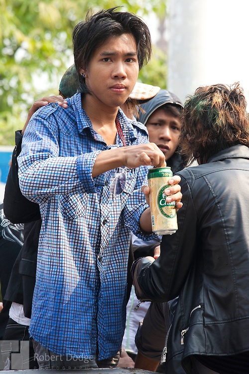 Mandalay, Myanmar- April 14, 2013: A young many opens a beer during Myanmar's Thingyan Water Festival. Thingyan is held in April, one of the hottest months of the year in Myanmar. The water festival marks the country's New Year celebration and the festival includes lots of drinking, singing, dancing and theater. Wherever you are you are likely to get doused with water as the Burmese see this as a cleansing of the previous year's sins and bad luck and a blessing for good luck and prosperity in the year ahead. In the major cities of Mandalay and Yangon, large platforms are erected along major roadways and are equipped with high powered water hoses. The platforms, sponsored by large corporate donors, also have dance stages and play the latest pop and hip hop music. Thousands of residents pour into the streets by foot, motorbike and flatbed truck to get hosed under the platforms while they drink and dance. Many of the young celebrants wear their best clubbing clothes. And many of the party goers are men, having left their wives and girlfriends at home.