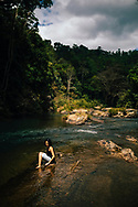 A young woman sits at a river in a valley of the Knuckles Mountain Range, Kandy, Sri Lanka, Asia