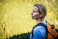 A head and shoulders portrait of a woman wearing a backpack looking out on an expanse of trees, Little Si trail, Washington USA.
