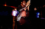Young man clapping and dancing at a club.