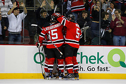 Dec 10, 2008; Newark, NJ, USA; New Jersey Devils right wing Jamie Langenbrunner (15) and New Jersey Devils defenseman Colin White (5) celebrate a goal by New Jersey Devils center Travis Zajac (19) during the second period at the Prudential Center.