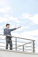 Young businessman with arm raised standing at terrace railings against sky