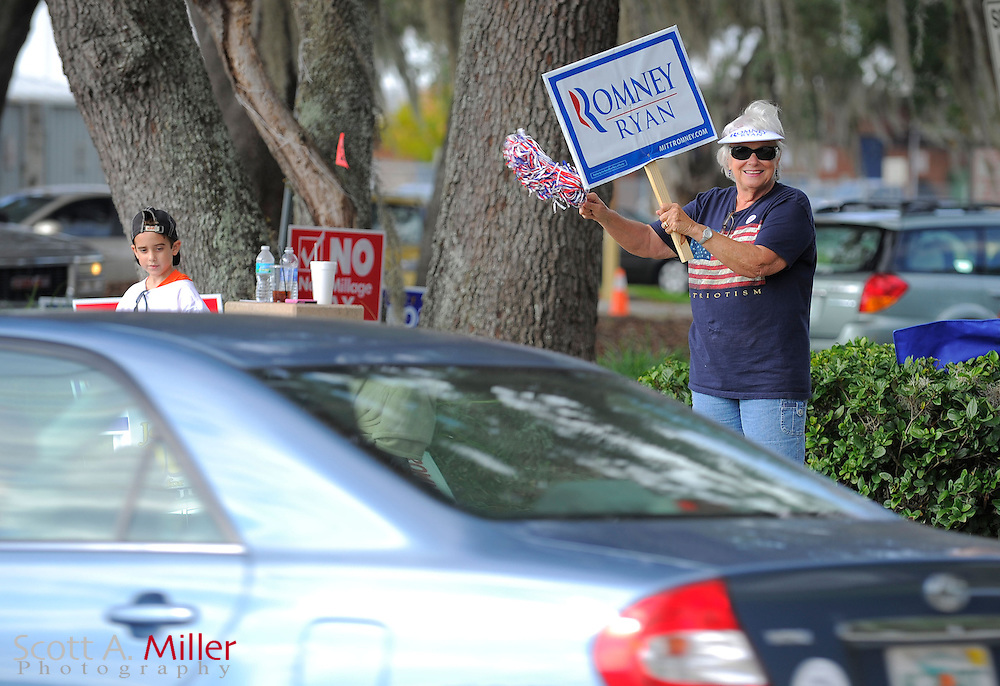 Julie Page waves to cars as they pull into the Northwest Branch Library to take part early voting in Lake Mary, Florida October 20, 2012.  ©2012 Scott A. Miller.