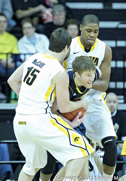 January 14, 2011: Michigan Wolverines forward Evan Smotrycz (23) tries to keep the ball away from Iowa Hawkeyes forward Zach McCabe (15) and Iowa Hawkeyes forward Melsahn Basabe (1) during the NCAA basketball game between the Michigan Wolverines and the Iowa Hawkeyes at Carver-Hawkeye Arena in Iowa City, Iowa on Saturday, January 14, 2011. Iowa defeated Michigan 75-59.