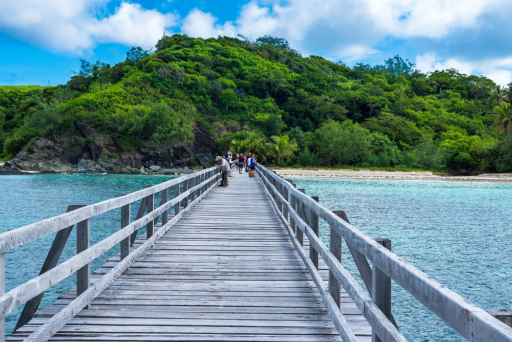Yasawa-I-Rara, Fiji--March 8, 2018. Tourists are walking down a long wooden dock toward lush foliage on thier way to a beach in the Fiji Islands. Editorial Use Only.