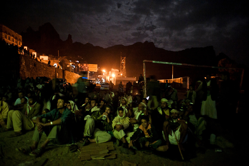 Spectators watch a semi-final match of the World Cup on a soccer  pitch in the town of Manakha, Haraz mountains, Yemen on 20th June, 2010. Members of the local council hooked up a video projector each evening of the World Cup on the soccer pitch in the middle of the town. The matches were projected onto a white sheet hanging on a wall of the town hall.