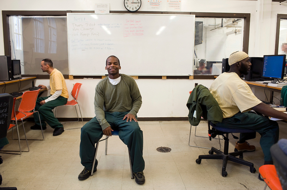 """(photographer's note: the faces of some inmates in the back room are digitally altered by the photographer in order to protect their anonymity).Woodbourne Correctional Facility inmate and Bard College student John Dickerson in the computer room...Story: The Bard Prison Initiative.Former inmate Carlos Rosario, 35-year-old husband and father of four, was released from Woodbourne Correctional Facility after serving more than 12 years for armed robbery. Rosado is one of the students participating in the Bard Prison Initiative, a privately-funded program that offers inmates at five New York State prisons the opportunity to work toward a college degree from Bard College. The program, which is the brainchild of alumnus Max Kenner, is competitive, accepting only 15 new students at each facility every other year. .Carlos Rosario received the Bachelor of Arts degree in social studies from the prestigious College Saturday, just a few days after his release. He had been working on it for the last six years. His senior thesis was titled """"The Diet of Punishment: Prison Food and Penal Practice in the Post-Rehabilitative Era,"""".Rosado is credited with developing a garden in one of the few green spaces inside the otherwise cement-heavy prison. In the two years since the garden's foundation, it has provided some of the only access the prison's 800 inmates have to fresh vegetables and fruit...Rosario now works for a recycling company in Poughkeepsie, N.Y...Photo © Stefan Falke"""