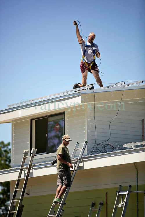 26 August 2015. New Orleans, Louisiana. <br /> Hurricane Katrina revisited. <br /> Rebuilding the Lower 9th Ward. <br /> Contractors prepare to install solar panels on a new 'Make it Right' house. Eco friendly 'Make it Right' houses inspired by actor Brad Pitt continue to provide hope for the rebirth of the community following the devastation of hurricane Katrina a decade earlier.<br /> Photo credit&copy;; Charlie Varley/varleypix.com.