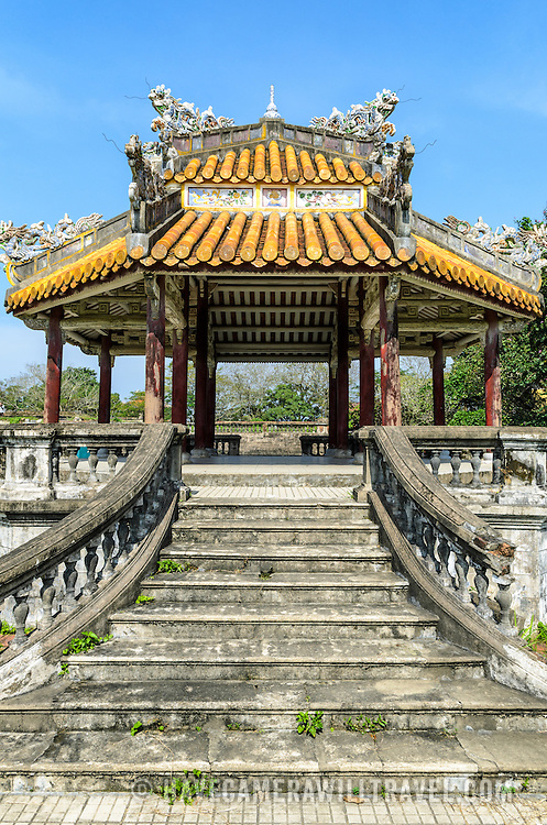 A restored pagoda, with its sweeping stairs, at the Imperial City in Hue, Vietnam. A self-enclosed and fortified palace, the complex includes the Purple Forbidden City, which was the inner sanctum of the imperial household, as well as temples, courtyards, gardens, and other buildings. Much of the Imperial City was damaged or destroyed during the Vietnam War. It is now designated as a UNESCO World Heritage site.