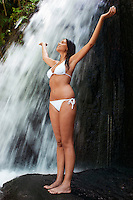 Young woman standing by waterfall with hands outstretched full length