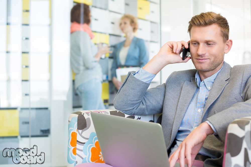 Businessman using technologies with colleagues discussing in background at creative office