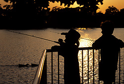 Stock photo of the silhouette of two boys fishing from a fenced pier at sunset