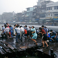 Thailand, Bangkok..Transport. Weather. Rain. Monsoon. Commuters on their way to work, surprised by sudden heavy rain fall as they disembark from long-tailed river ferry boat on the Chao Phraya River...©Mark Henley