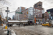 A large silver truck crosses the intersection of East Houston and Bowery Lower East Side, New York City, New York, Unites States of America.  The green Bowery New York Street Sign has been decorated with the word David in tribute to the rock star David Bowie who died in January 2016, the same month that the city experienced a record breaking snowstorm, some snow piles can still be seen on the side of the road. (photo by Andrew Aitchison / In pictures via Getty Images)