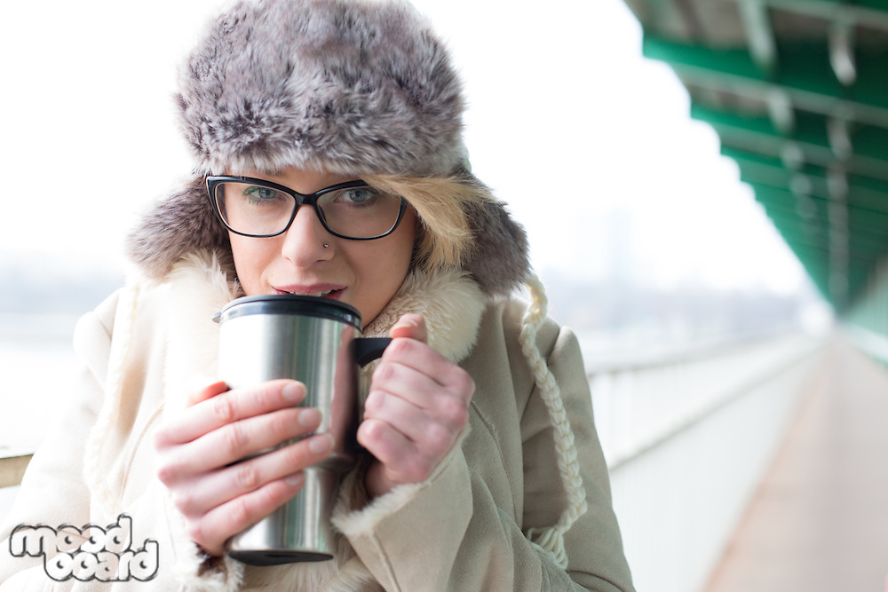 Portrait of woman drinking coffee from insulated drink container during winter