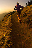 A young woman runs along the Dog Mountain Trail in the Columbia River Gorge, Washington.