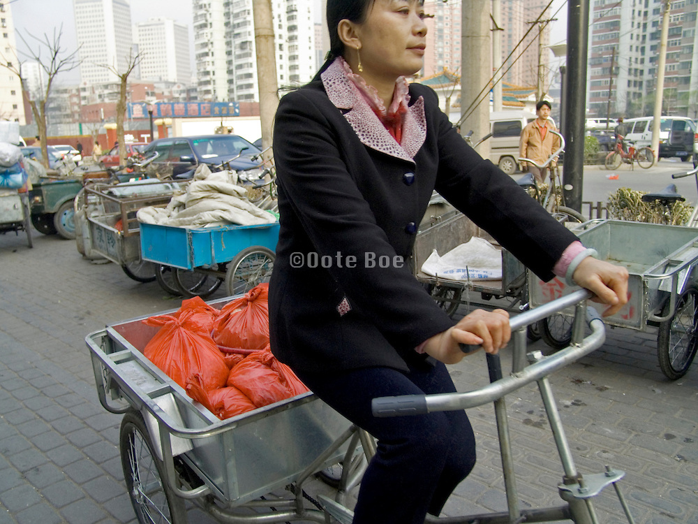young female using an bicycle cart to transport her groceries to her home Beijing China
