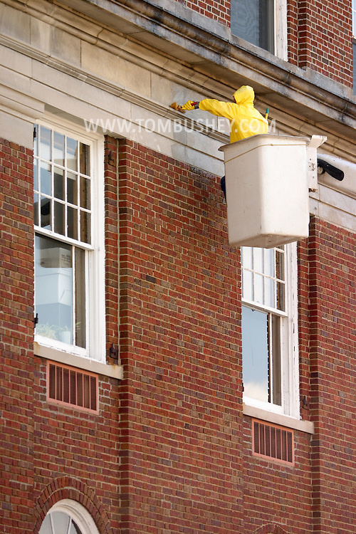Middletown, N.Y. - A worker in a bucket truck cleans the stonework above the second-floor windows at City Hall on May 13, 2006. ©Tom Bushey