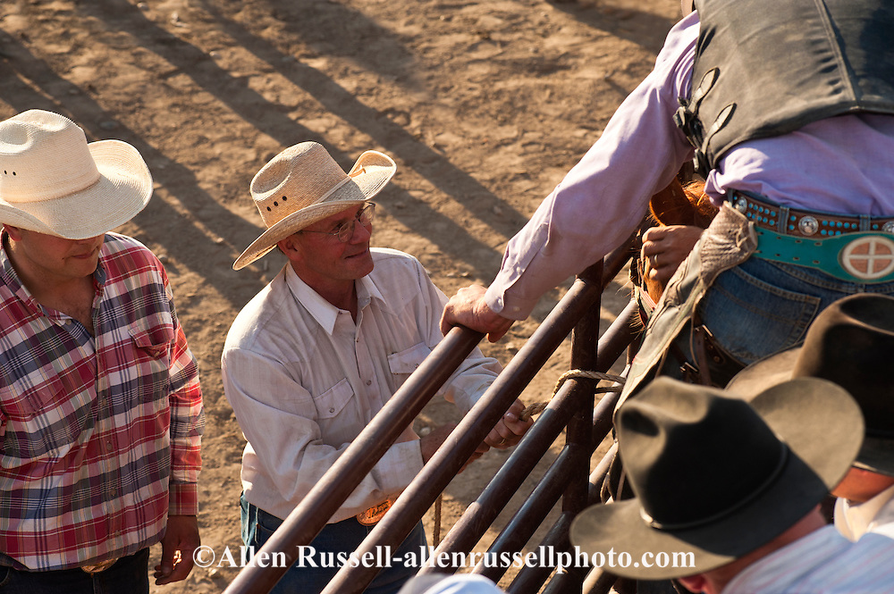 Pat Linger, Chute Boss at Miles City Bucking Horse Sale, Montana, helps Saddle Bronc rider