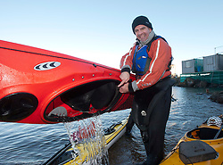 Scottish Sun sports editor Iain King tales empties water from his kayak after taking part in a practise session for his charity kayak challenge, in the waters of the harbour at St Abbs..Pic © Michael Schofield...