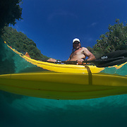 Naturalist Ron Leidich in a kayak at Mandarinfish Lake in Risong Bay, Palau. Ron leads kayak tours through the Rock Islands of Palau.