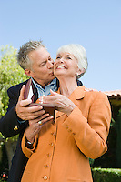 Senior man kissing wife on cheek and giving present