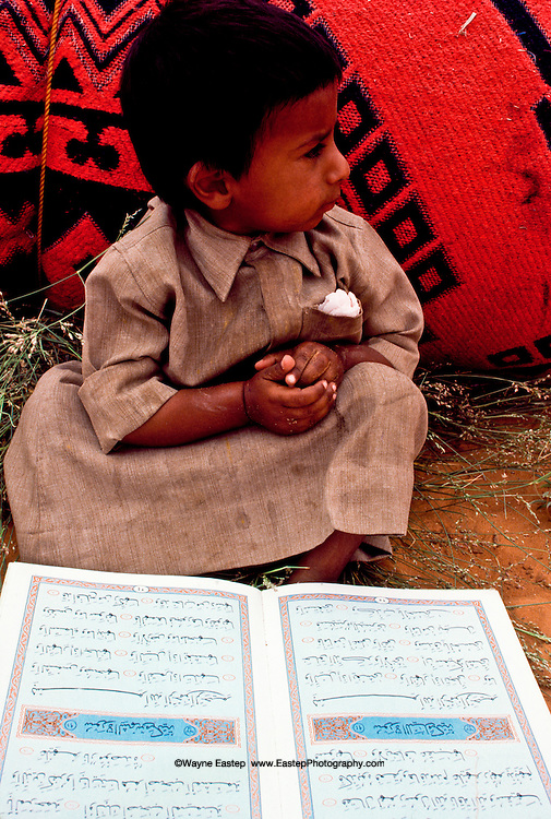 Jaber Al Amrah in front of his cousin's Qur'an at  Al Murrah encampment in the Dahana Sands, Saudi Arabia