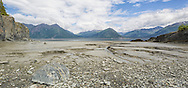 Composite panorama of channels in the silt of Turnagain Arm created by low tide near Hope with the Chugach Mountains in the background near Anchorage in Southcentral Alaska. Summer. Afternoon.