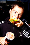 A young boy eating a fast food burger and holding a drink.