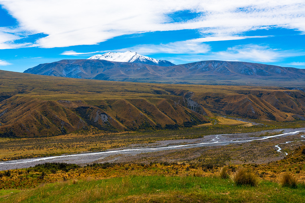 A stream meanders quietly through a long valley in New Zealand