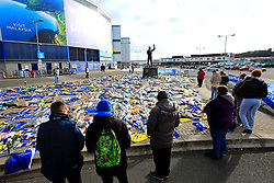 A view fans looking on at the flowers and scarves placed outside Cardiff City Stadium in tribute to Emiliano Sala during the Premier League match at the Cardiff City Stadium.
