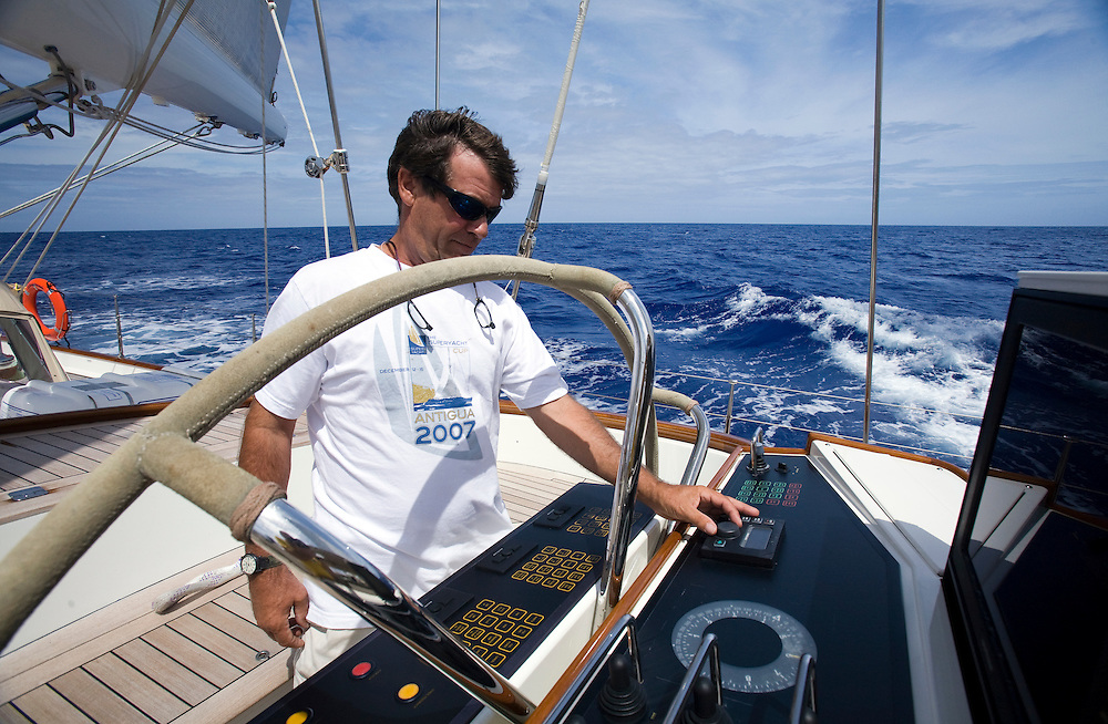Crew member Robbie Cooke adjusts the auto pilot on board the 155ft sailing ketch Scheherazade. Modern mega yachts are dominated by electronics to the point where the wheel is rarely touched.