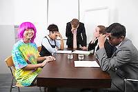 Tired multiethnic businesspeople with colleague in pink wig at meeting