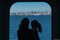 United States, Washington, Seattle, silhouette of mother and daughter looking at Seattle through ferry window