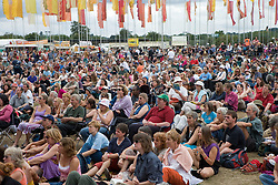 Crowd listening to band of musicians playing on stage at the WOMAD (World of Music; Arts and Dance) Festival in reading; 2005,