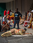 A costumed performer rests on the street after all night dancing in the annual New Year Junkanoo Parade on January 1, 2013 in Nassau, Bahamas. The carnival like festival is celebrated in the early hours of the New Year lasting until the late morning and dates back to slavery days.