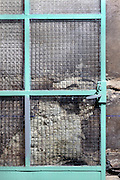 metal door frame with safety glass against an old wall