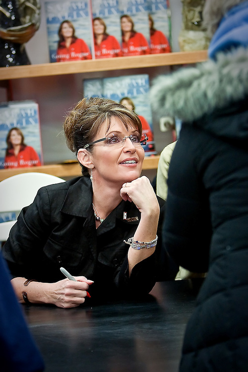 JEROME A. POLLOS/Press..Sarah Palin listens to a autograph seeker who was among hundreds of people who waited in line to meet the former vice presidential candidate Thursday during a book signing event held in Coeur d'Alene.