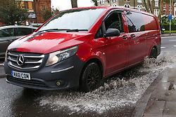 © Licensed to London News Pictures. 14/10/2019. London, UK. A van drives through a large puddle of water left on Tottenham High Road after heavy overnight rainfall in north London. According to the Met Office more than two inches of rain could fall this afternoon. Photo credit: Dinendra Haria/LNP
