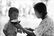 C009-6_Tom Huchins_Young woman (as in C009-2) feeding boy watermelon, Peking, China 1956 A3.tif