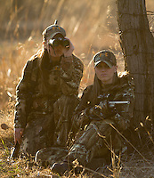 ONE DEER HUNTER SHOOTING A RIFLE WHILE THE OTHER HUNTER WATCHES THROUGH BINOCULARS